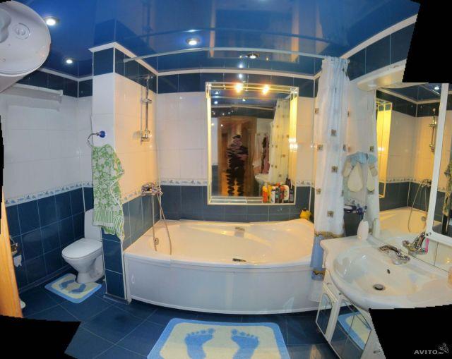 фотограф отражается в зеркале при фотографировании ванной